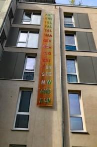 Spruchband an Hausfassade: Artenvielfalt Klimagerechtigkeit Systemwandeln