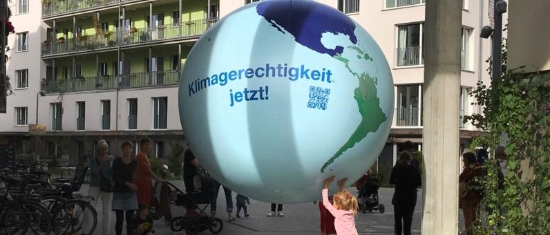 Bannerfoto:Mädchen hält eine Weltkugel auf der steht: Klimagerechtigkeit jetzt