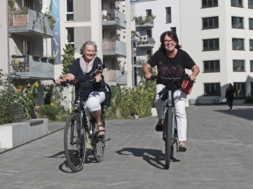 zwei mittelalte bis ältere Frauen auf dem Fahrrad auf der Kiezstraße