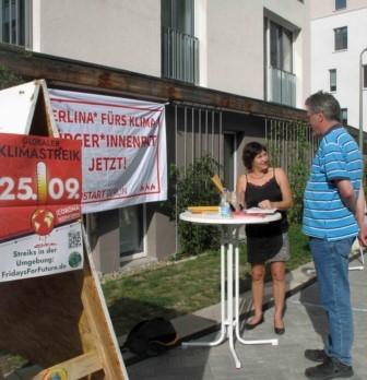 Hinweisplakat Klimastreik 25. September, zwei Personen am Stand für Klima Bürgerinnenrat Berlin