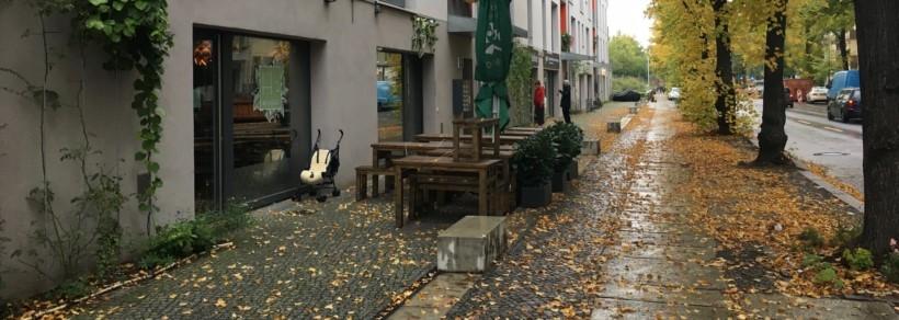 herbstliche nasse Möckerstraße mit gelben Blättern und leeren Tischen des Veggie Restaurants