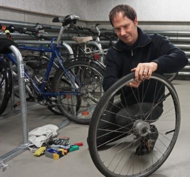 Mann bearbeitet ein Vorderrad im Keller