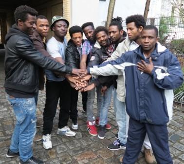 9 afrikanische Geflüchtete halten ihre Hände zu einem Turm zusammen