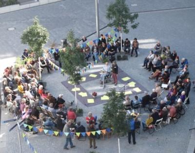 Blick von Oben: Viele Menschen sitzen im Kreis auf dem Kiezplatz