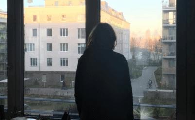Frau schaut aus dem Fenster auf die Kiezstrasse