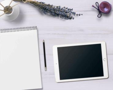 Symbolisches Foto mit Schreibblock und Laptop