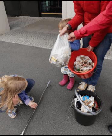 Kinder werfen Müll in einen Eimer